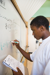 A student solves a problem on a dry-erase board